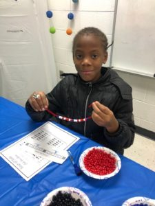 Student creating a Binary Bracelet using beads and a pipe cleaner.
